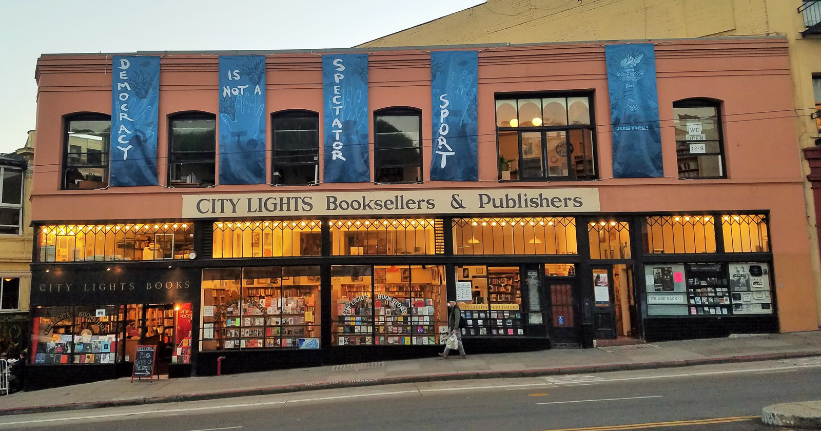 Lighted up City Lights storefront with banners that read DEMOCRACY IS NOT A SPECTATOR SPORT