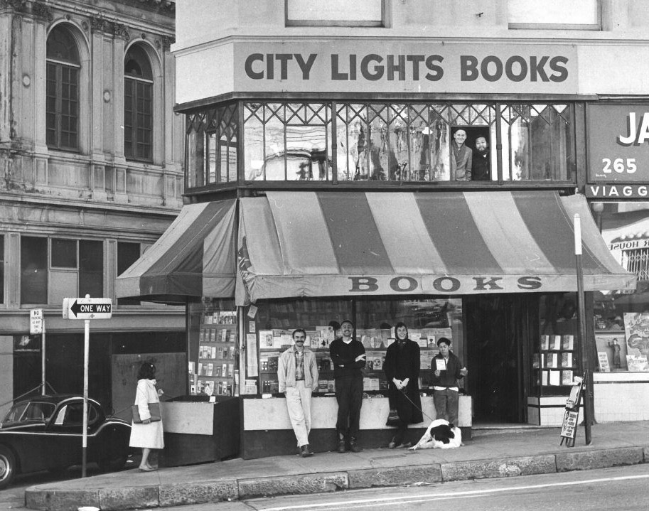 Four smiling patrons outside the original, smaller City Lights storefront, circa mid-1950s
