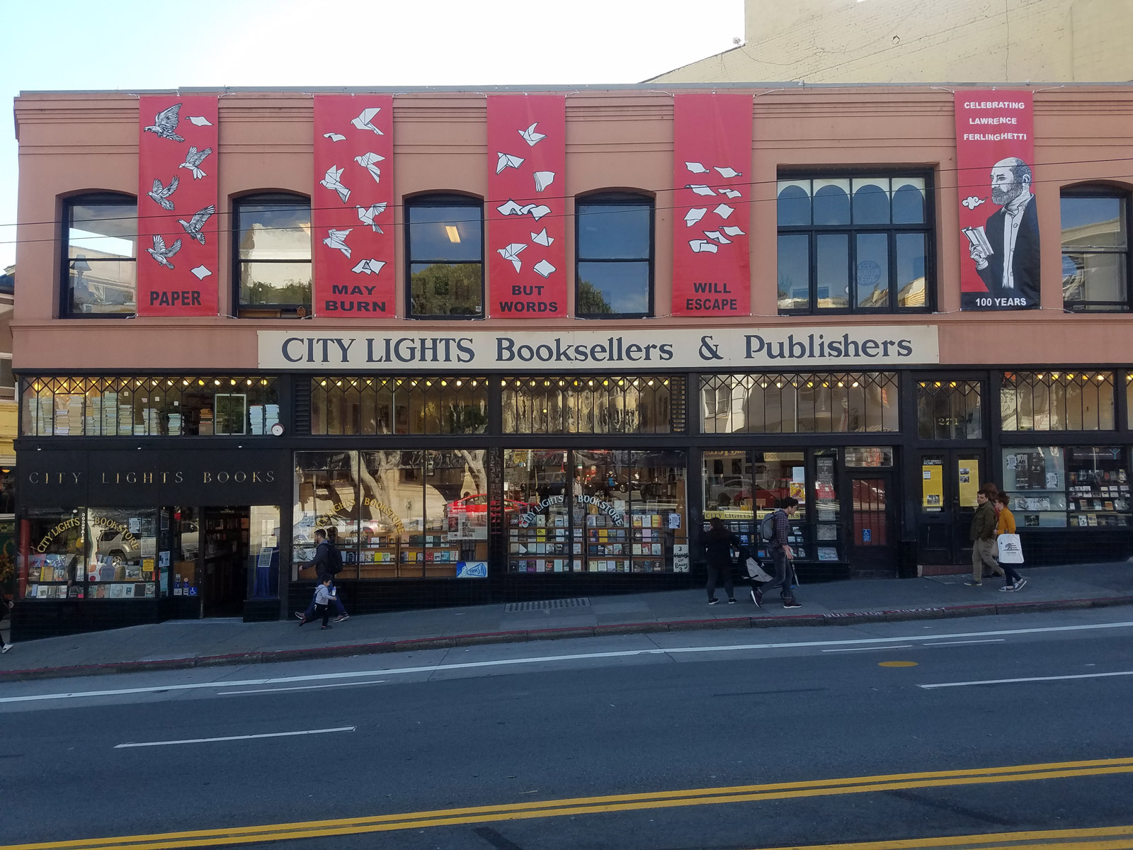 People walk by the City Lights storefront that is decorated with banners for Ferlinghetti's centennial