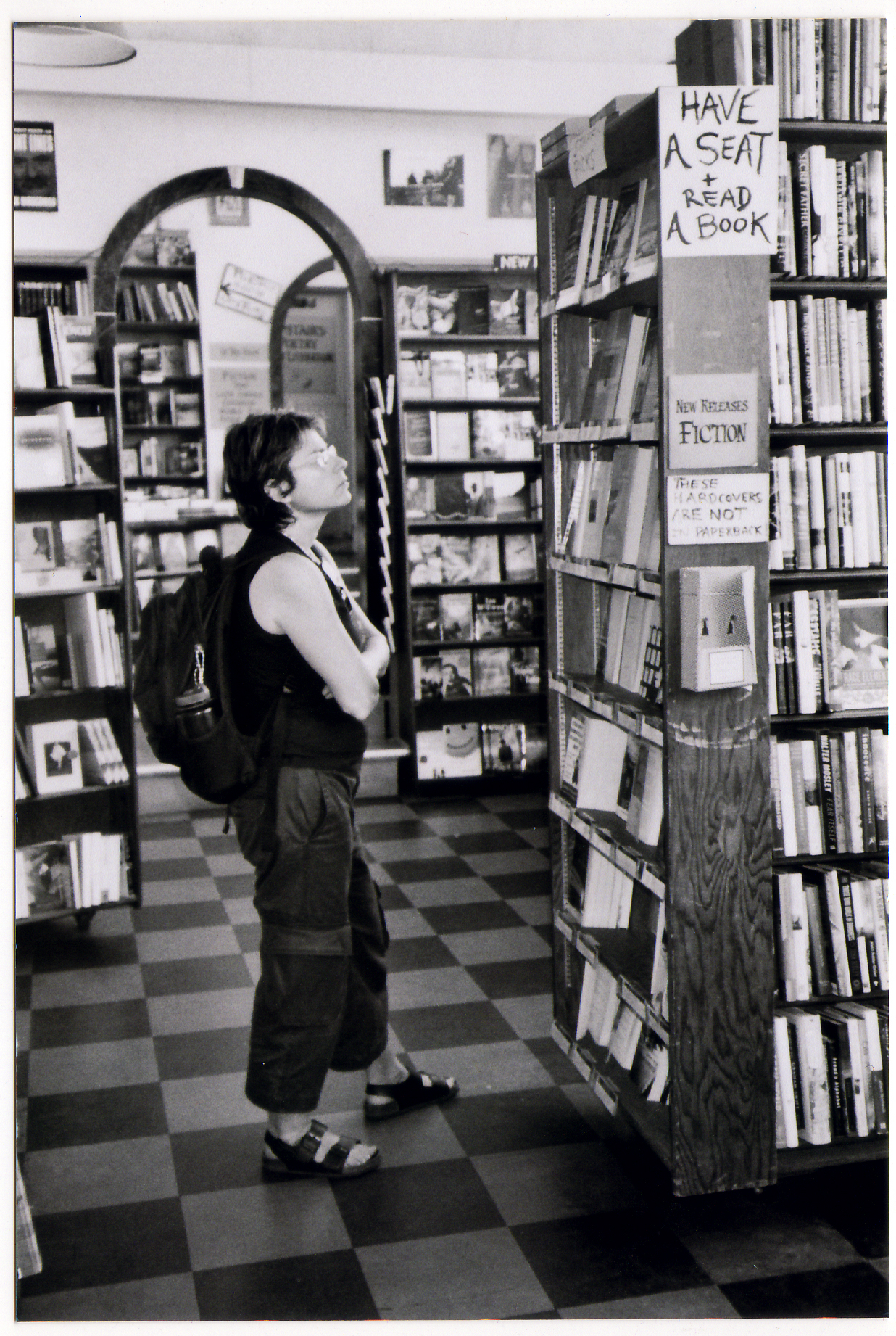 Woman studying a bookshelf in the City Light main room