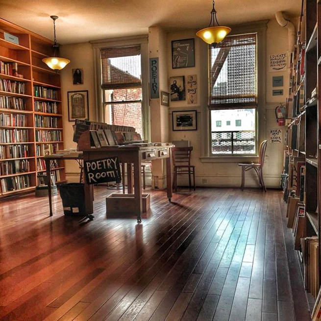 The upstairs poetry room, filled with bookshelves and a central table, in daytime
