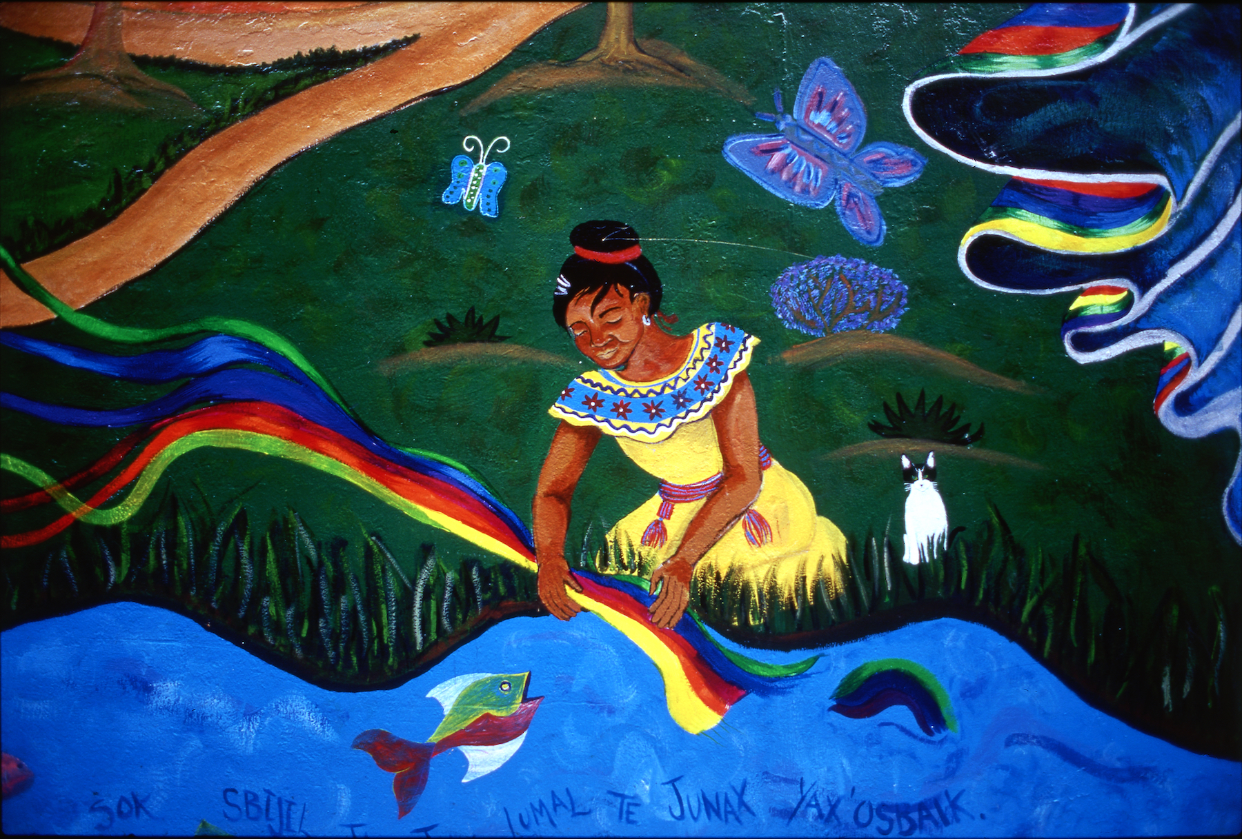 Mural depicts a woman wetting a multi-colored cloth in a rushing river. Fish swim by