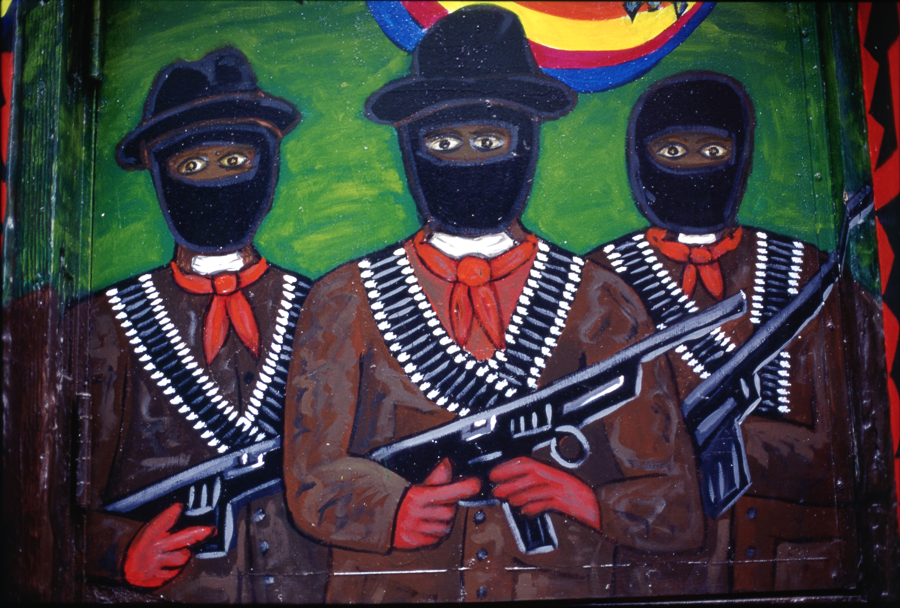 Close-up of section of mural that depicts three masked Zapatista fighters with guns