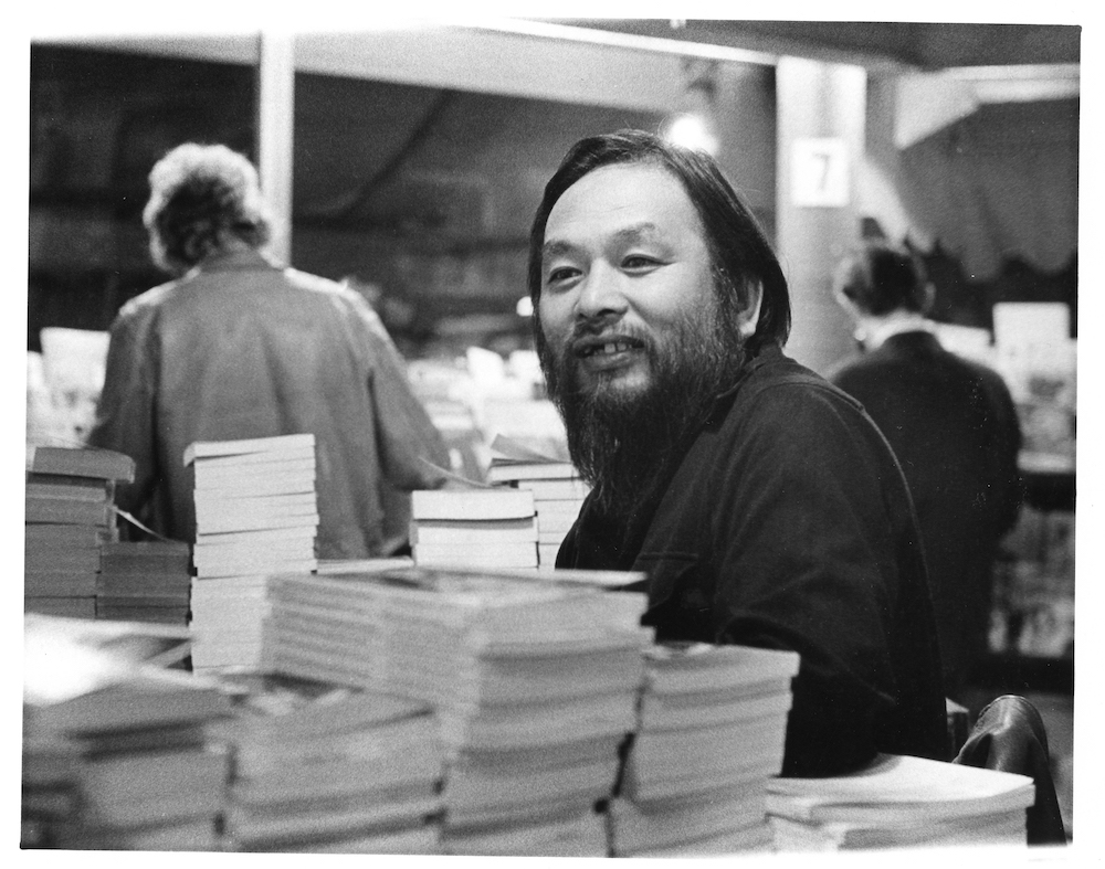 Portrait of a smiling Shigeyoshi Murao behind stacks of books
