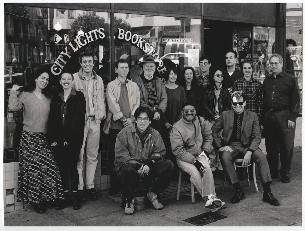 Group shot of 15 smiling City Lights staff members posing outside the storefront