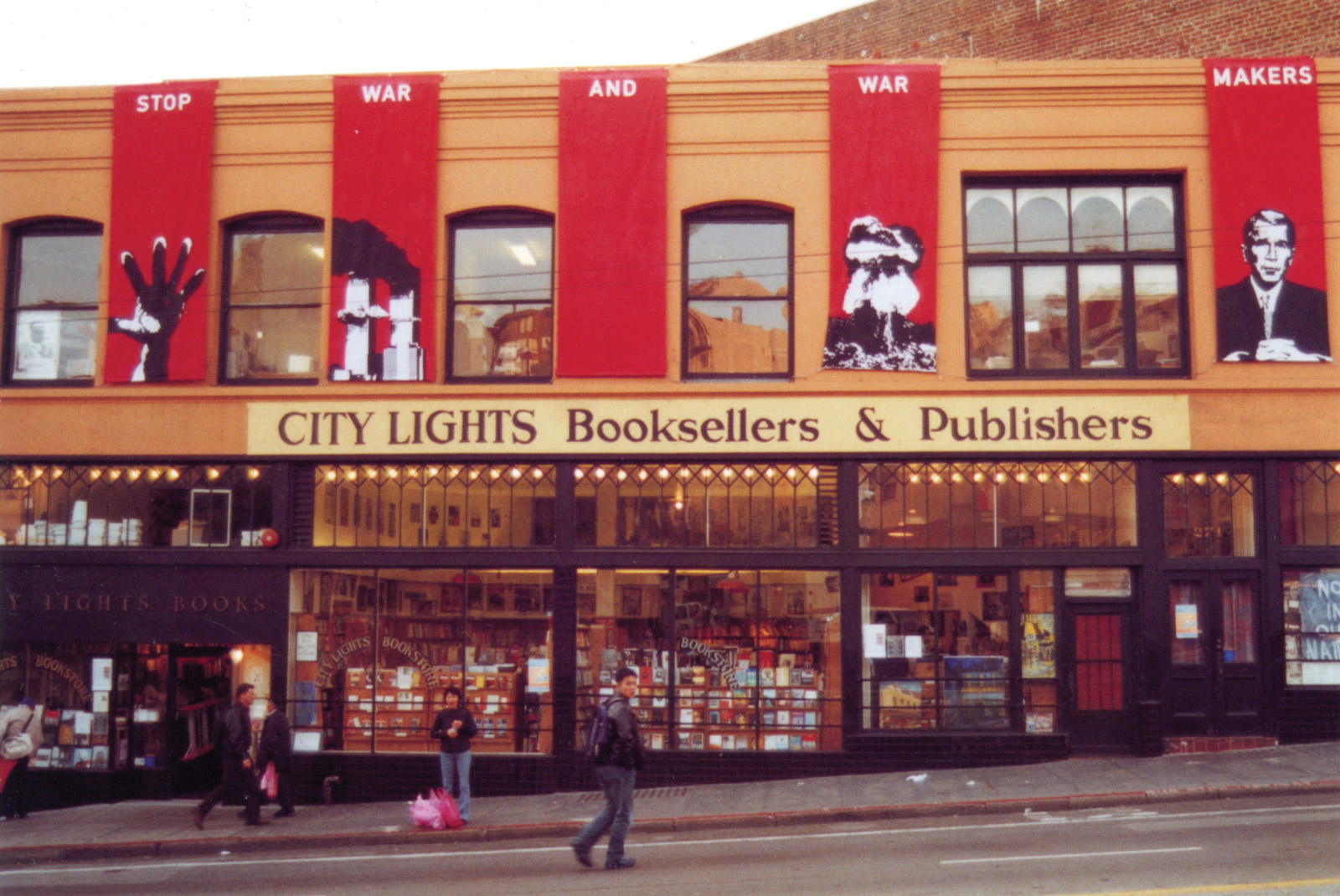 Few people walk by the City Lights storefront that is decorated with large red banners