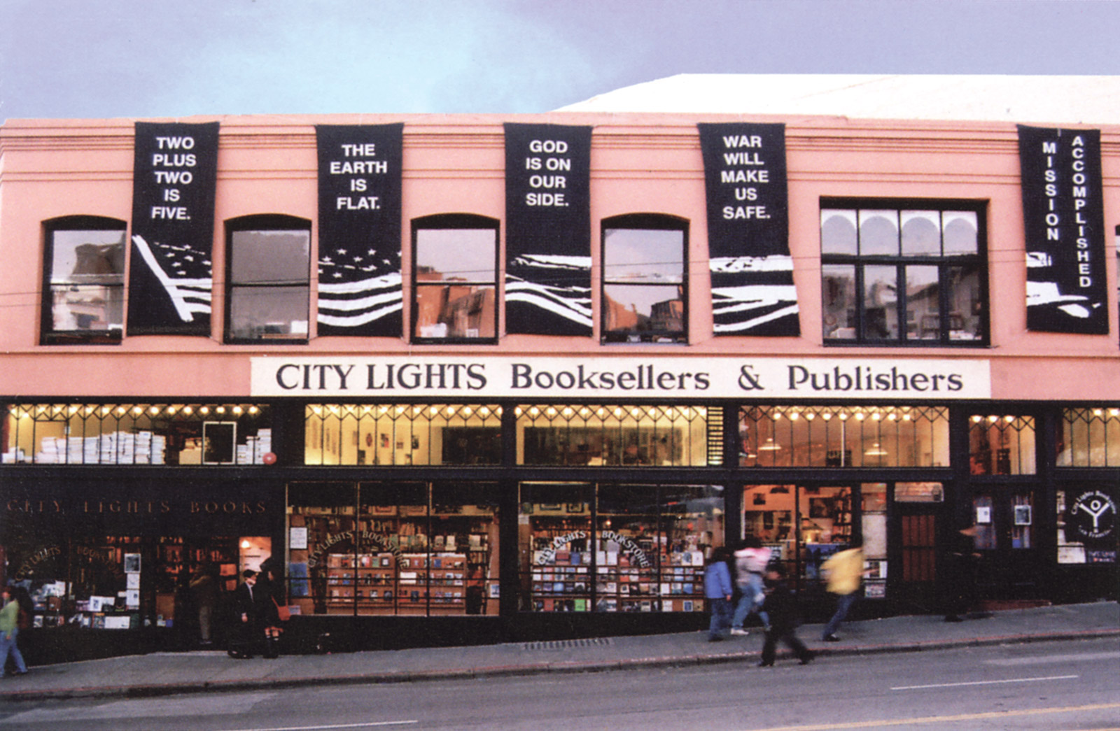 People walk by a lighted up City Lights storefront that is decorated with large black banners