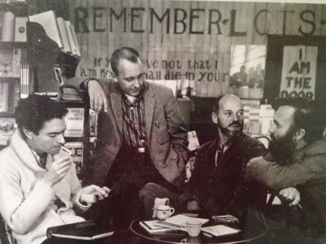 Ferlinghetti and three other men drinking coffee at a table in the City Lights bookshop, circa 1953