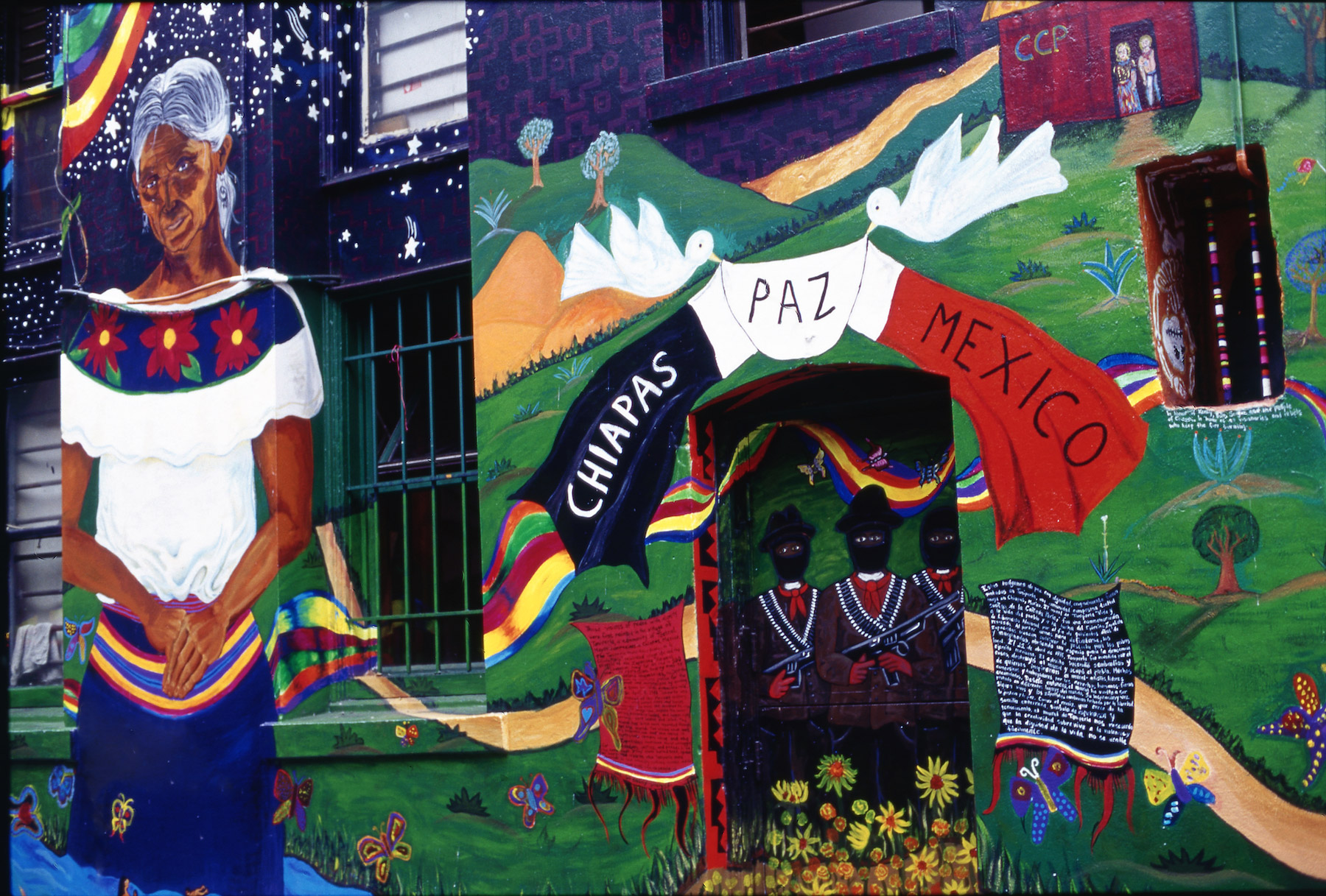 Section of mural that depicts Zapatista fighters and a smiling Indigenous Mexican woman
