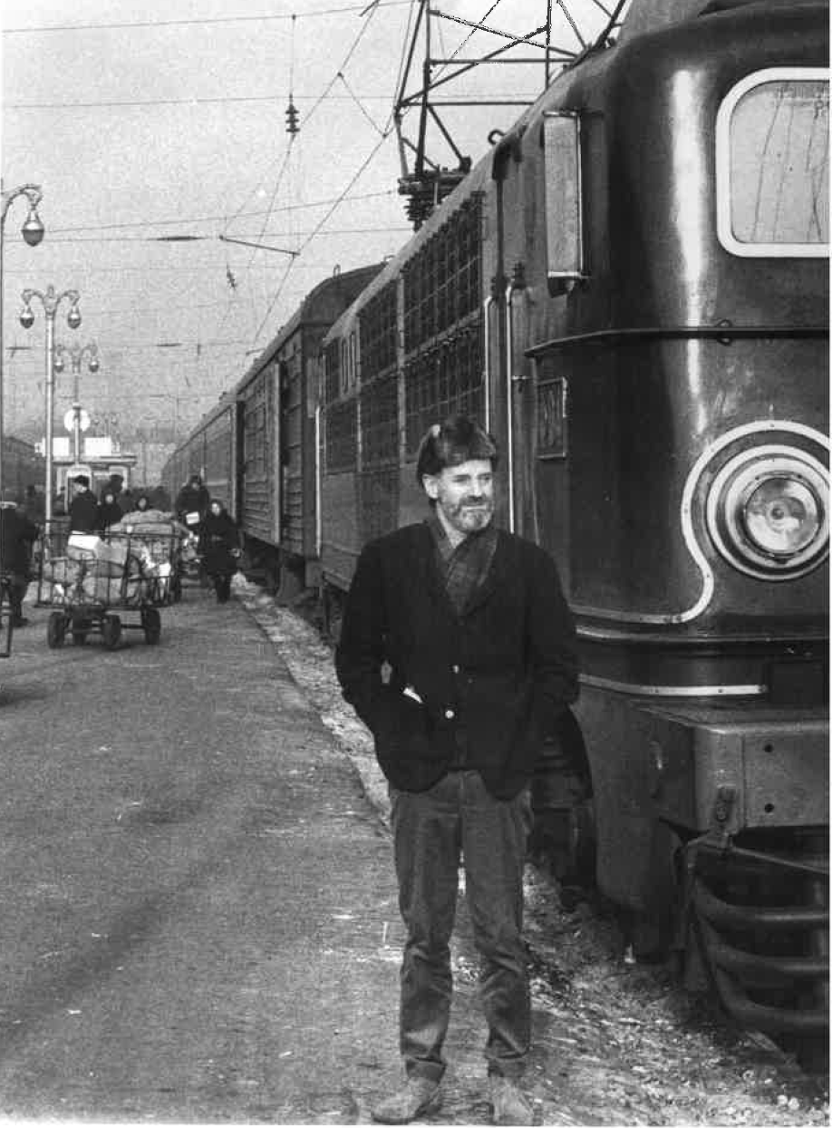 Ferlinghetti wearing a Russian fur hat and posing in front of a large passenger train