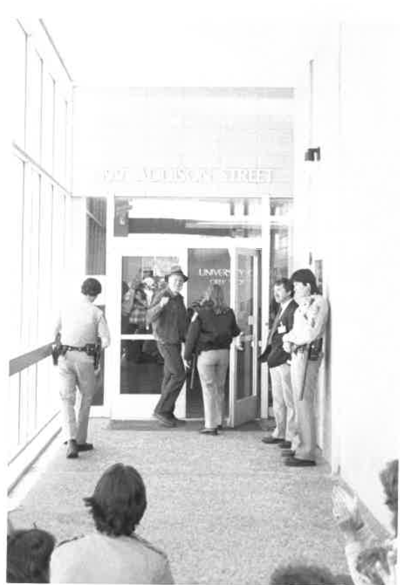 Ferlinghetti being escorted into a UC Berkeley building by campus police