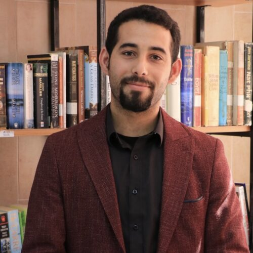 Mosab Abu Toha standing in front of a bookshelf with hands crossed in front
