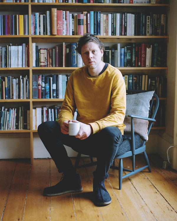 author max porter sitting in a chair in front of a bookcase with a coffee cup in his hand, looking at camera